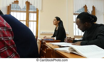 Students at University Writing in Copybooks - Group of...
