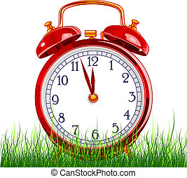 Summer Time - Red vintage alarm clock in Green grass on...