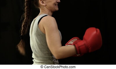 Girl in boxing gloves - Girl with boxing gloves on a black...
