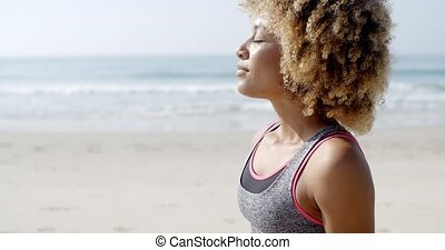Fit Woman Sits On The Beach - Fit smiling woman sits on the...