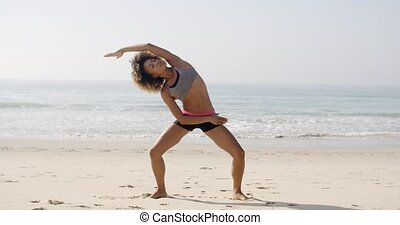 Yoga Meditation On The Beach - Woman practices yoga on the...