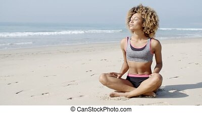 Woman Sitting On The Beach In Lotus Pose - African american...