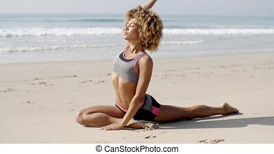 Woman Practicing Yoga At Seashore - Young woman practicing...