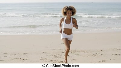 Woman Jogging On The Beach - Athletic young african american...