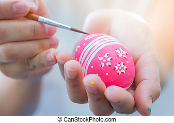 Woman hand  decorating Easter eggs