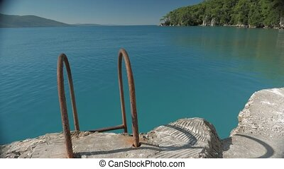 Bath ladder with rusted handrails leading up from the sea to steep pier. 4