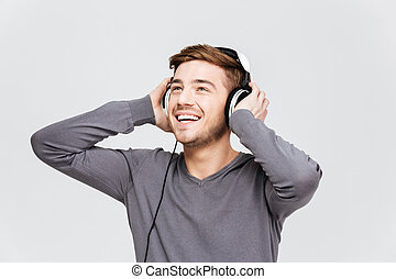 Cheerful attractive young man in headphones listening to...