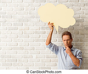 Man with speech bubbles - Thoughtful middle aged man is...
