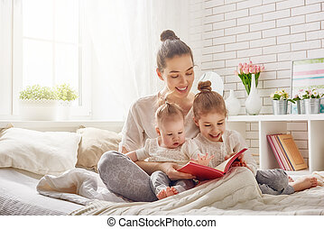 mother reading a book - happy loving family. pretty young...