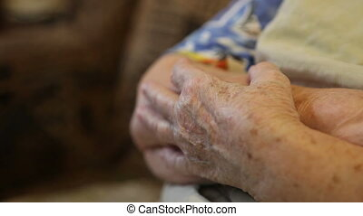 the folded hands of the elderly woman close-up