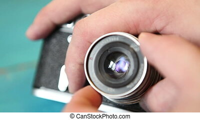 man opens and closes the aperture on the lens of an old...