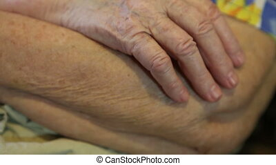 the folded hands of the elderly woman