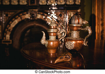 vintage still life with antique teapots , bird copper  skull and  bottles with tea and grass in bottles