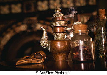 vintage still life with antique teapots and bottles with tea and grass
