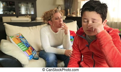 Mother smoking near her coughing child - Mother sitting on a...