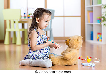 kid playing a doctor in children room - kid girl playing a...
