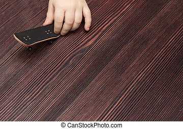 Fingerboard on wooden background in hands of the baby