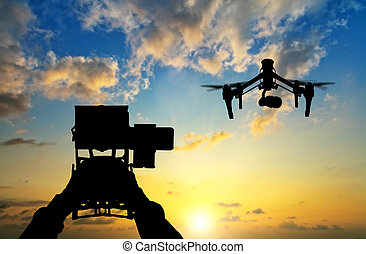 Man hands handling drone in sunset silhouettes - Man hands...