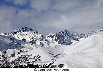 Snowy off-piste slope and mountains in clouds Caucasus...