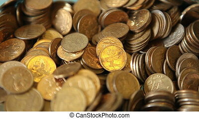 metal coins falling into a pile, close-up HD