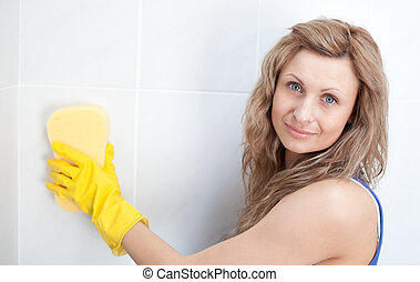 Young woman cleaning a bathroom