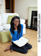 Chrming woman reading a book sitting on the floor