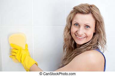 Smiling woman cleaning a bathroom