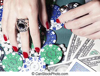hands of young caucasian woman with red manicure at casino...