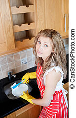 Unhappy woman doing the dishes in the kitchen