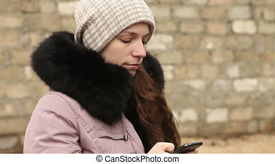 woman writing sms in winter clothes on smartphone