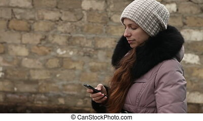 woman writing sms in winter clothes on smartphone -...