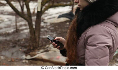 girl writes sms in winter clothing outdoors rear view