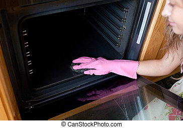 Close-up of a woman cleaning the oven in the kitchen