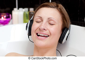 Smiling young woman listening music in a bubble bath -...