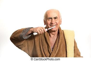 old man brushing his teeth - old senior man brushing his...
