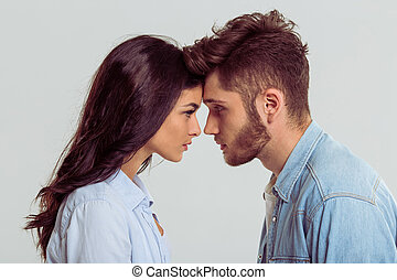 Beautiful young couple in jeans shirts standing head to head...