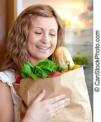 Charming woman holding a grocery bag in the kitchen