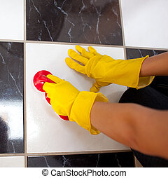 Close-up of a woman cleaning the floor with a sponge and...