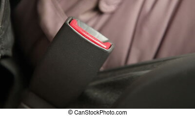 female hands wear a seat belt in the car, close-up