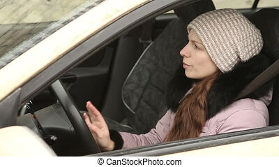 woman in winter clothes sings while driving - beautiful...