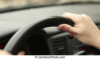 female hands on the steering wheel of the car, close-up