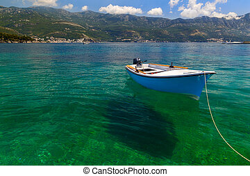 Small fishing boat is moored at the coast in transparent...