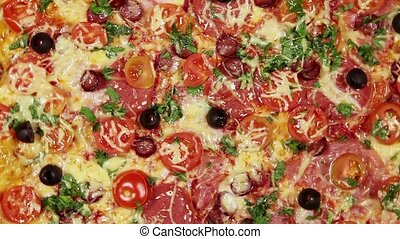 Rotating pizza with cheese, tomato - Full frame video of...