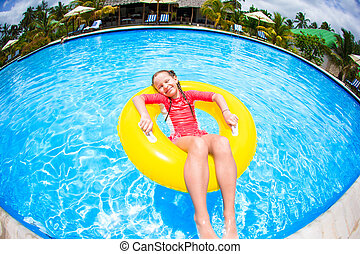 Little girl with inflatable rubber circle having fun in...