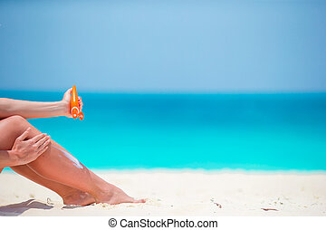 Slim woman applying sunscreen on her legs, sitting on sandy...