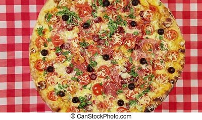 Front view video of rotating pizza with cheese, tomatoes and...