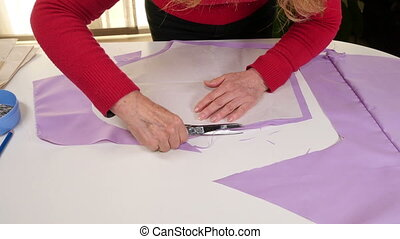 Seamstress Cutting Clothes Pattern - Dressmaker working in...