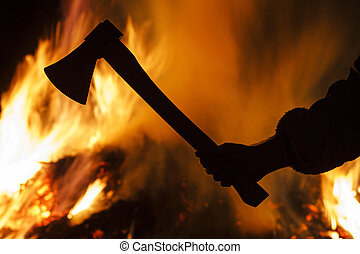 hand with an ax on a background of a burning forest,...