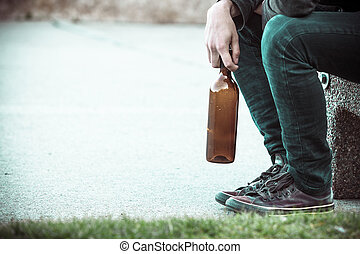Man depressed with wine bottle sitting on bench outdoor...