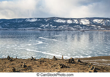 Beautiful winter landscape with mountains on the frozen lake Baikal against cloudy sky. Smooth surface of ice with a pattern of cracks and snow.